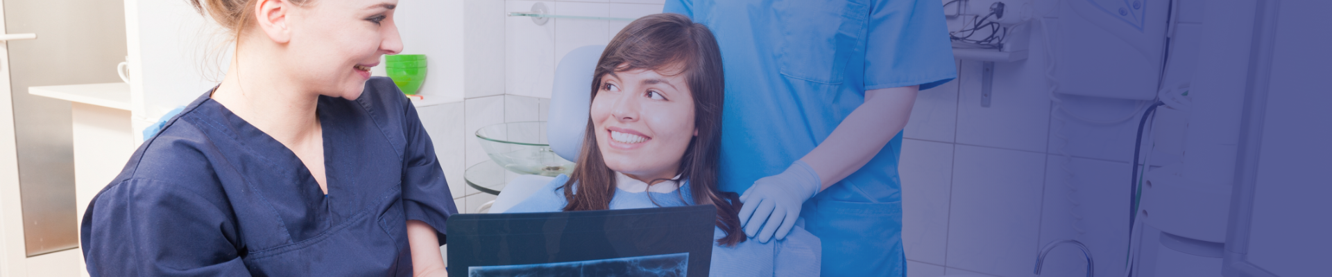 Dentist and assistant showing x ray image to patient